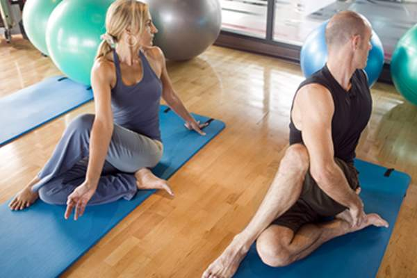 Man and woman doing the seated spinal twist yoga pose.