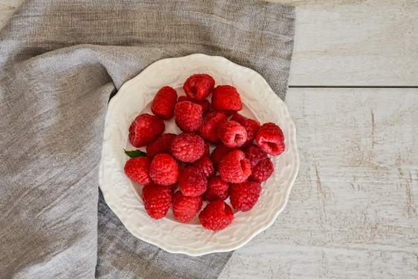 raspberries in a bowl on top of grey napkin and wood table