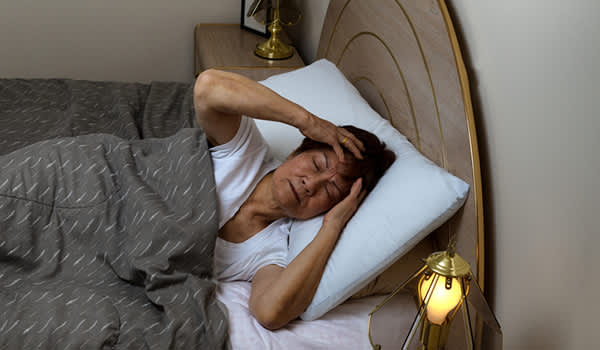 older woman having trouble sleeping image