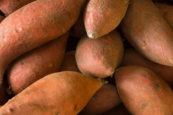 Whole raw sweet potatoes.