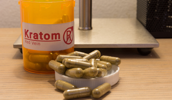 Kratom pill bottle and pills on nightstand.