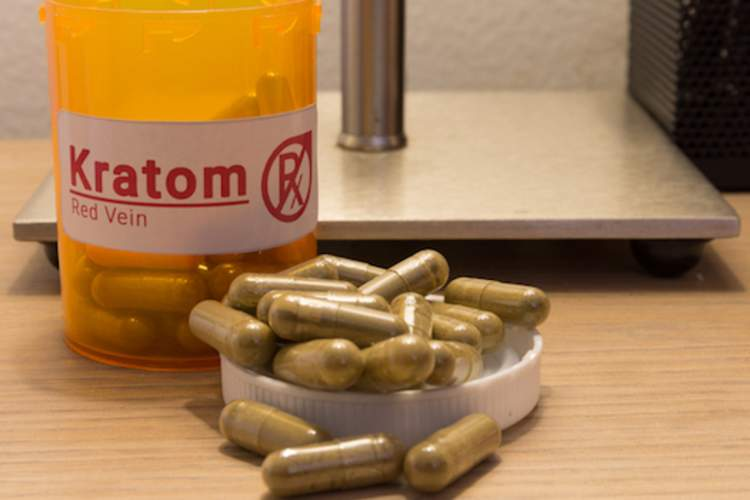 Kratom pill bottle and kratom capsules on a nightstand.