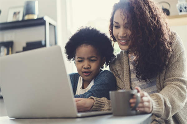 Mother and young daughter on laptop.