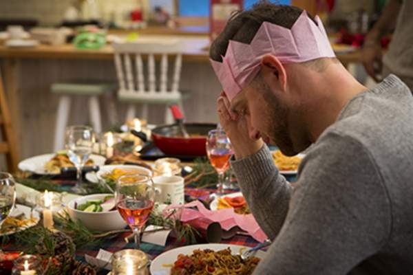 Man looking sad at a holiday dinner.