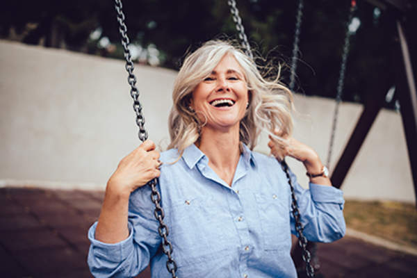 Laughing woman having fun on a swing set.