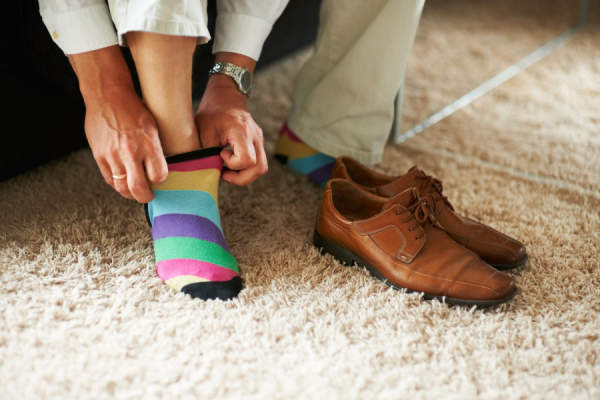 man putting striped socks and brown shoes on