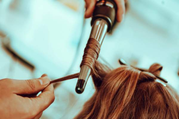 hairdresser curling client's hair