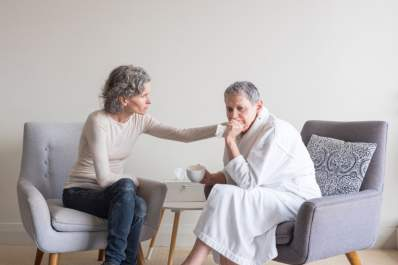 Senior woman in robe being comforted by middle aged woman