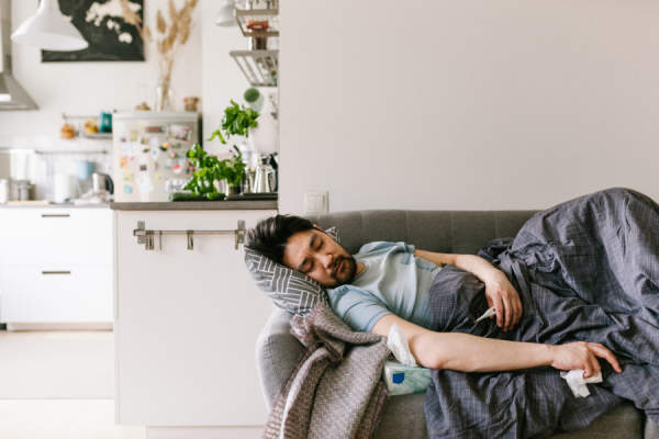 man sick and sleeping on couch