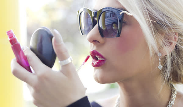 Young blonde woman applying lip gloss image.