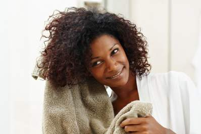 Smiling woman drying her hair with a towel.