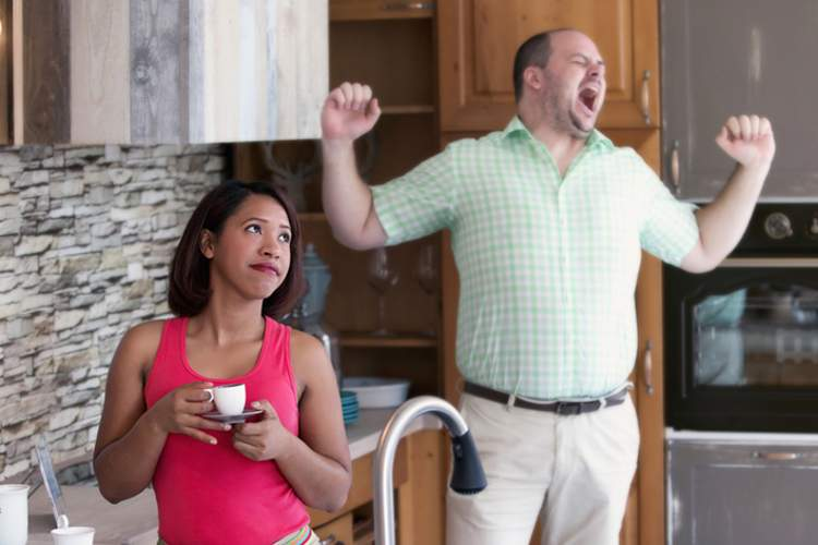 Overweight man yawning it kitchen, woman drinking tea.