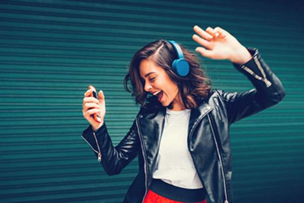 Teen girl dancing with headphones on.