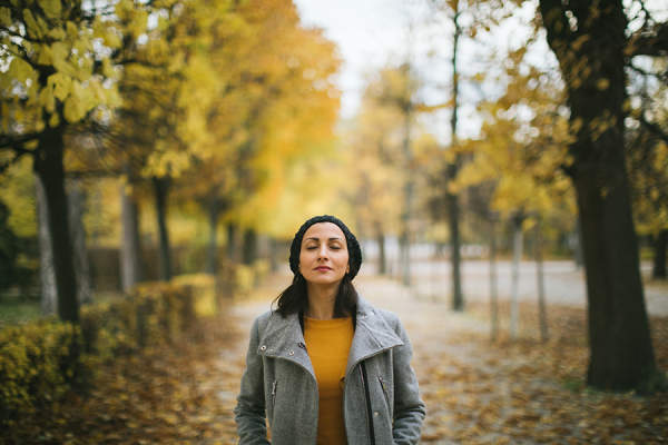Woman taking a deep breath while walking outdoors
