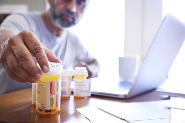 Man sitting at table reaching for prescription medication