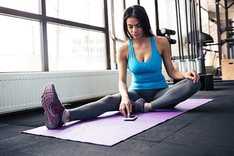 Young woman sitting on yoga mat and using smartphone