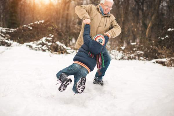 Grandfather playing with grandchild in snow.