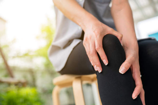 Young woman holding knee in pain