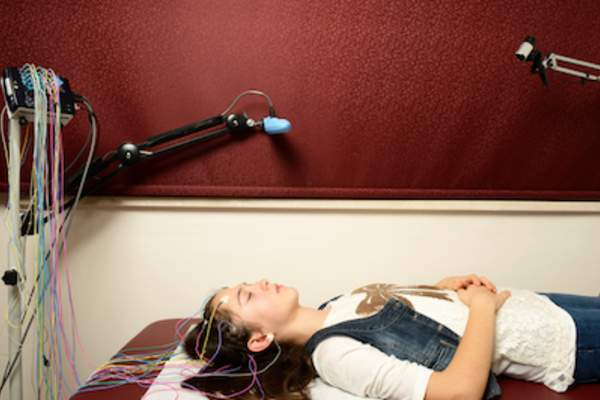 Woman undergoing electroencephalography to study brain activity while asleep.