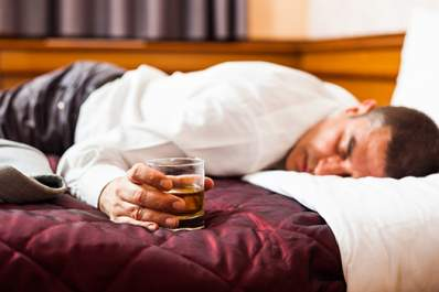 Man asleep face down on a bed holding a glass of whiskey.