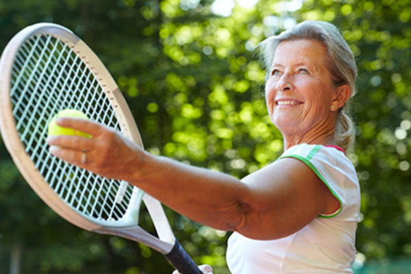 Senior woman playing tennis.