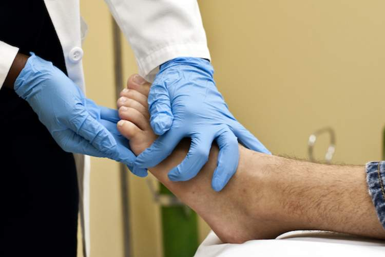 A doctor checks a patient's foot for diabetic foot ulcers.