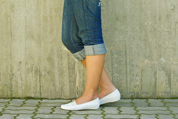 Woman wearing white flats.