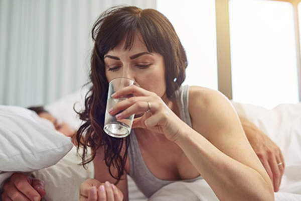 Woman drinking water in bed.