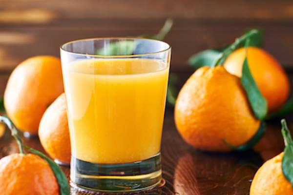 Glass of fresh orange juice and oranges.
