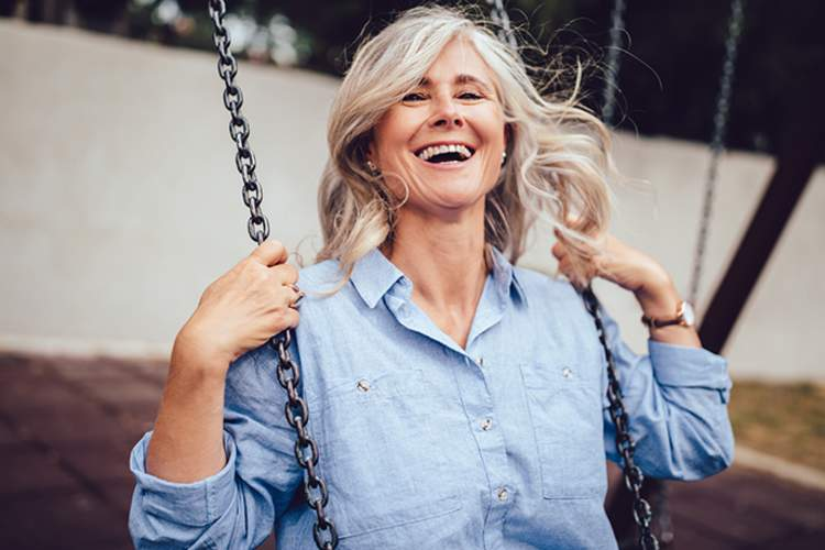 Middle age woman having fun on a swing set.