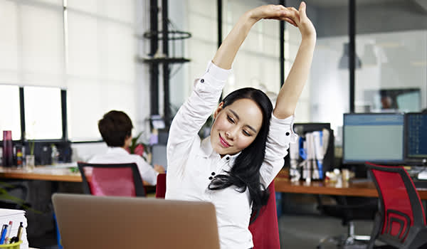 Asian business woman stretching arms in office