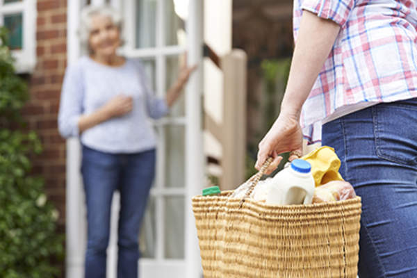 Woman helping her neighbor with groceries.