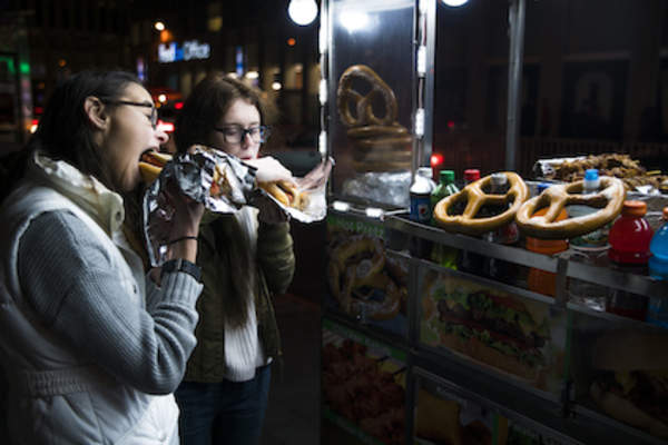 Eating at street vendor late in the evening.