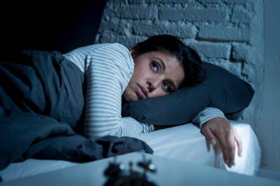 Woman with insomnia having trouble sleeping at night.
