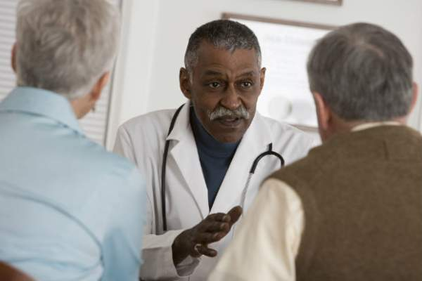 Male doctor talking to senior couple.