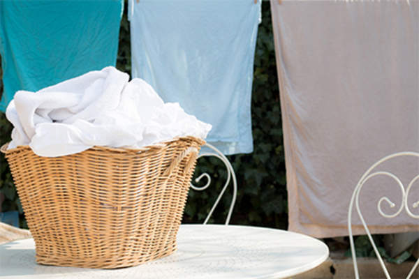 Laundry basket and sheets hung on clothes line.