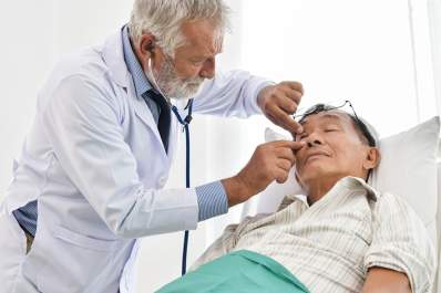Doctor examining senior man's eye while he lies down.