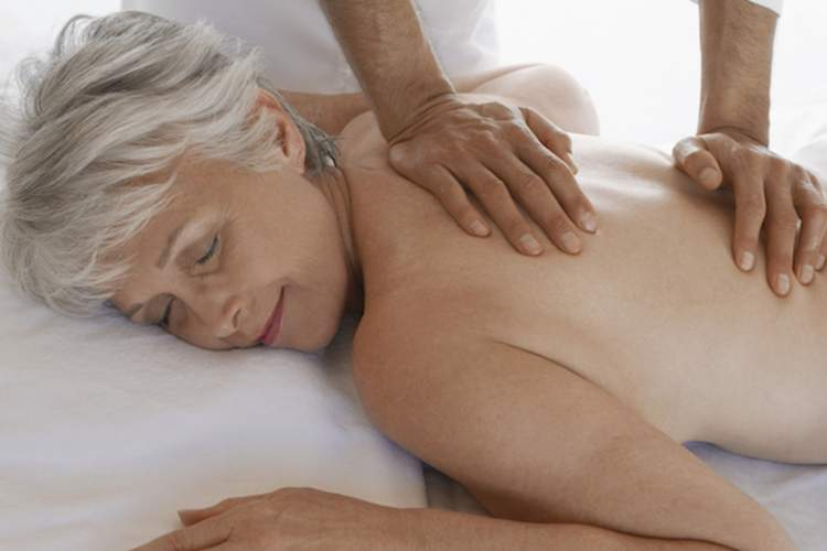An elderly woman gets a massage for back pain.