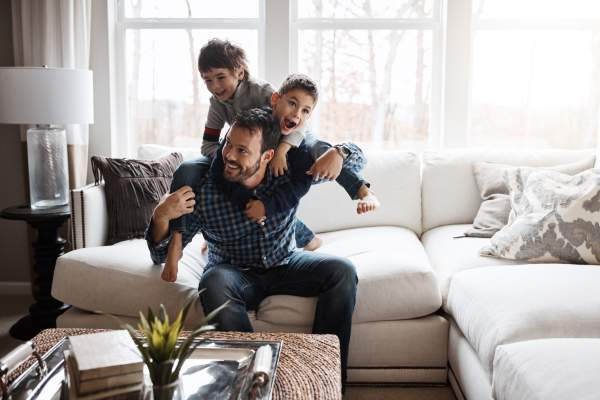 Father playing with two sons in living room