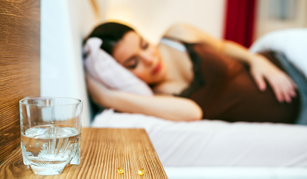 Pills and glass of water on nightstand, pregnant woman sleeping in background.