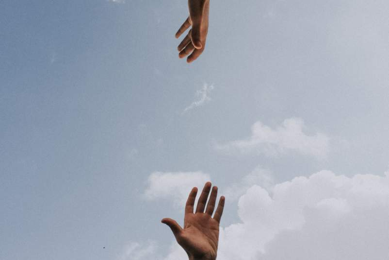 hands reaching for each other across sky