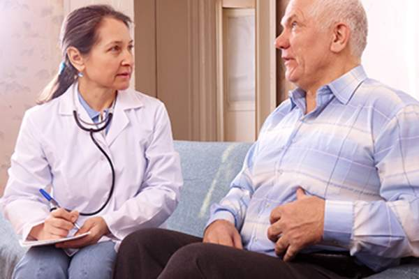 Senior man explaining stomach pain to his doctor.