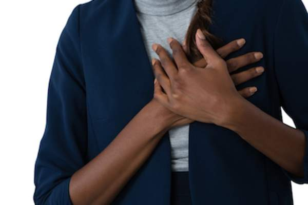 Woman with burning chest pain, holding chest.