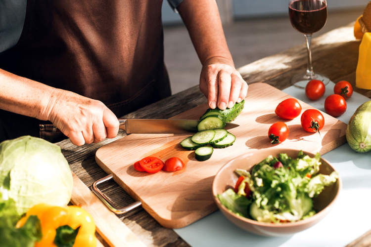 Woman cutting fresh vegetables on cutting board.