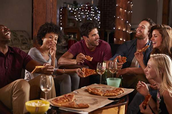 Young adults sharing pizzas at a party at home.