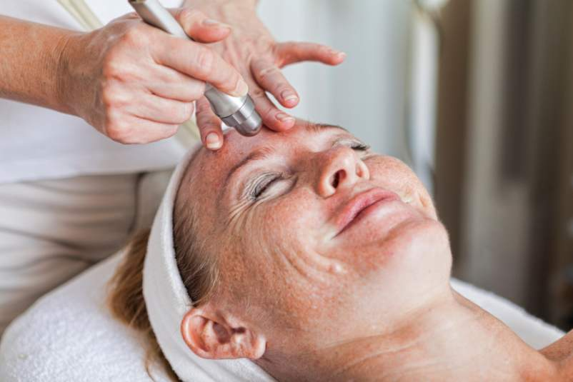 esthetician using tool on woman's face