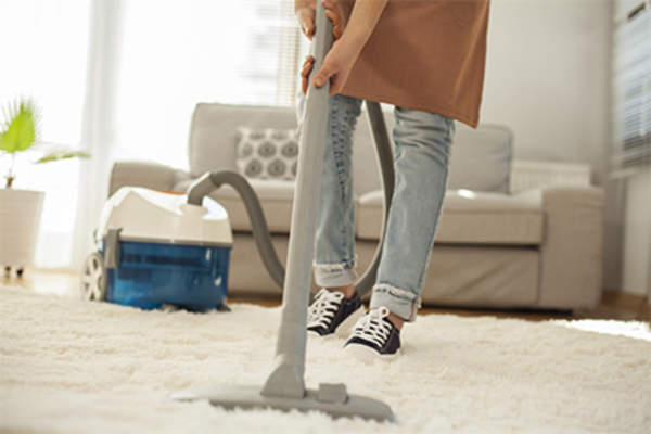 Woman using carpet cleaner.