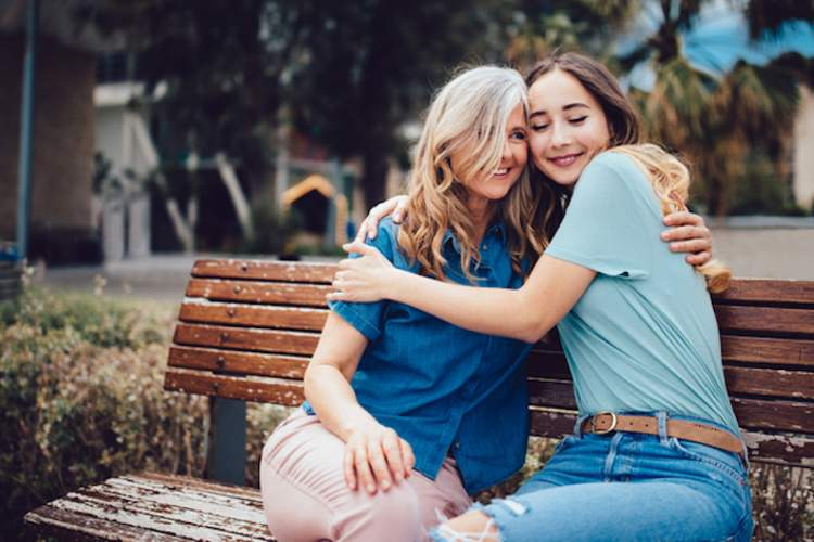 Mother and daughter embracing while sitting on a bench.