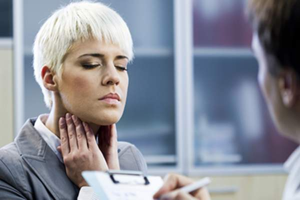 Woman with a sore throat seeing a doctor.