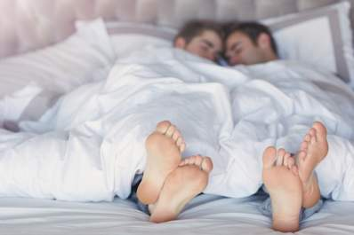 Couples feet sticking out from under covers in bed.